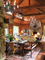 The main room of the log cabin is a large open-plan living/dining area with matching stone fireplaces at either end and a double-height ceiling