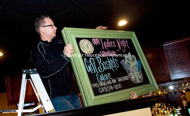 WATERBURY, CT - 10 NOVEMBER 2009 -111009JT15-<br /> As an incentive for more business, Brass City Bistro owner Thomas Gould hangs a chalkboard display advertising this week's local business that sponsors the restaurant's weekly raffle prize on Tuesday in Waterbury. <br /> Josalee Thrift Republican-American