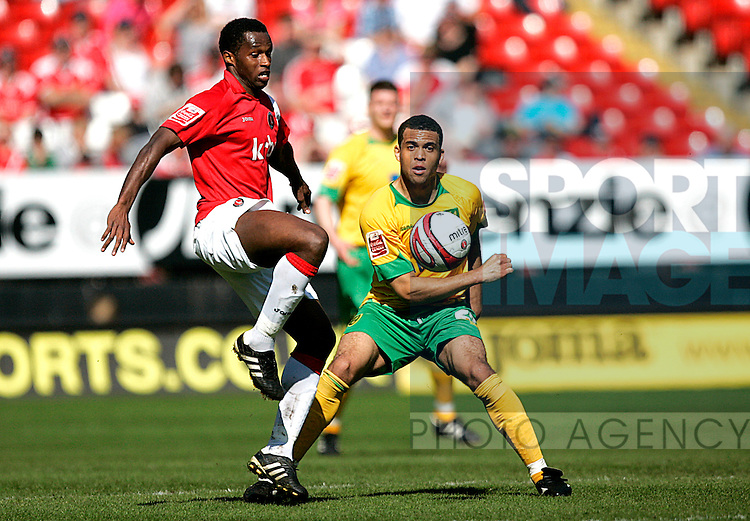 Jose Semedo of Charlton Athletic holds off Darel Russell of Norwich City