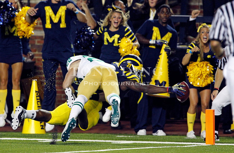 Michigan wide receiver Junior Hemingway, bottom, stretches under a tackle from Notre Dame safety Harrison Smith to score a touchdown in the second quarter of an NCAA college football game, Saturday, Sept. 10, 2011, in Ann Arbor, Mich. (AP Photo/Tony Ding)