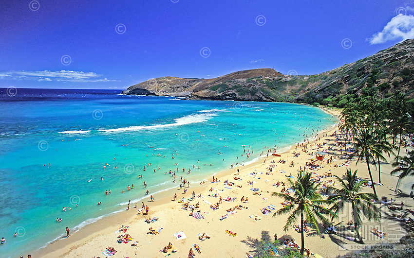A  perfect tropical day at Hanauma Bay with sunbathers and snorkelers enjoying the clear blue water and white sand crescent beach.