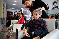 85 year old former farmer Zhang Tianyu enjoys a haircut near her relocation housing estate in the southwestern Chinese megapolis of Chongqing. She and her fellow villagers were moved from their farmland several years ago and resettled nearby in this purpose-built estate. She receives a pension of 1,000 yuan a month. A haircut normally costs 20 yuan, but the barber Liu Huan, 24 - himself a recent urban convert and who opened this shop four months ago - charges her 10 yuan. The Chinese government plans to move 250 million rural residents into urban areas over the coming dozen years though it is unclear whether people want to move and where the money for this project will come from. Further urbanisation is meant to drive up consumption to counterbalance an export orientated economy and end subsistence farming but the drive to get people off the land is causing tens of thousands of protests each year. /Felix Features