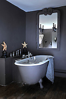 In this bathroom an antique theatrical mirror with sconces hangs above the roll-top bath