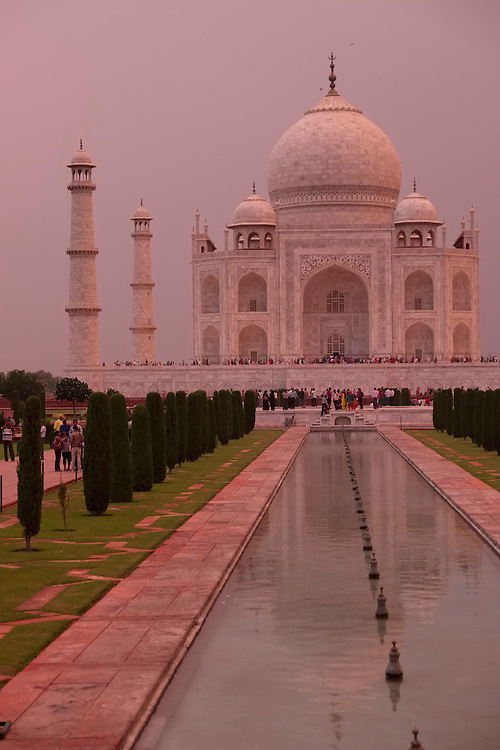 Last light of day is tinged with color from storm clouds as it lights the white marble mausoleum of Taj Mahal.