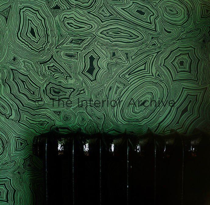 The wall behind a classic style radiator is hung with a green and black pattern wallpaper with a neo-pop motif.