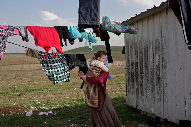 17/02/15 --TANJERO, IRAQ: Ghazal hangs up the family laundry while holding her grandson, Mazal.<br /> <br /> The family of Yezidis, displaced from Sinjar, live next to an oil refinery in the Kurdish Region of Iraq. The young men run the refinery 24 hours a day with little to no safety equipment. Reporting for this article was supported by a grant from the Pulitzer Center on Crisis Reporting