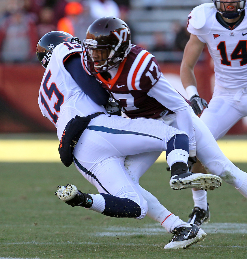 Nov 27, 2010; Charlottesville, VA, USA; Virginia Cavaliers quarterback Ross Metheny (15) is hit by Virginia Tech Hokies cornerback Kyle Fuller (17) during the game at Lane Stadium. Virginia Tech won 37-7. Mandatory Credit: Andrew Shurtleff-