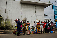 MONROVIA, LIBERIA - AUGUST 23, 2014:   Liberians, wait as they hold food to hand over to waiting friends and relatives unable to leave from the quarantined West Point neighbourhood, as a Liberian Police officer directs them forward up to the quarantine line, during the fourth day of the government's Ebola quarantine on West Point on August 23, 2014 in Monrovia, Liberia.  Liberia&rsquo;s government announced Friday night that it would lift an Ebola quarantine on a large slum here in the capital, 10 days after attempts to cordon off the neighborhood from the rest of the city sparked deadly clashes and fueled doubts about President Ellen Johnson Sirleaf&rsquo;s ability to handle the outbreak.<br /> <br /> Photo by Daniel Berehulak