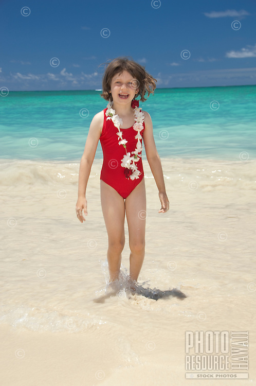 Young girl on white sand beach in red swimsuit and lei.