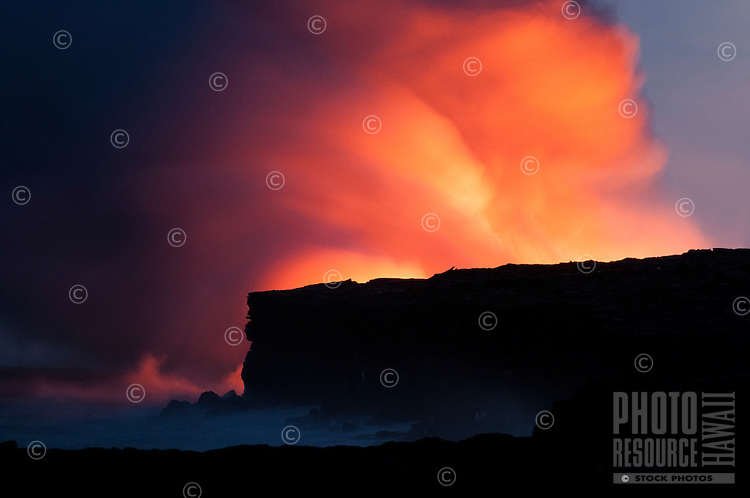 Molten lava flowing into the ocean lights up a steam cloud on the Big Island.