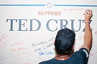 """Cruz supporter Bob Wilkonski of Newbury, NH, signs a wall after hearing Texas senator and Republican presidential candidate Ted Cruz speak to a crowd at the kick-off event at his New Hampshire campaign headquarters in Manchester, New Hampshire. One woman wrote """"In God and Ted We Trust!"""" Wilkonski wrote """"I want conservatism and liberty back!"""""""