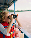 PERU, Amazon Rainforest, South America, Latin America, girl looking through binocular while travelling in boat along the Tambopata River.