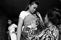 Children of Bassac. Teacher Nop Thyda is helping Sreyneang to adjust her krama, a traditional scarf, around her chest. Phnom Penh, Cambodia - 2007