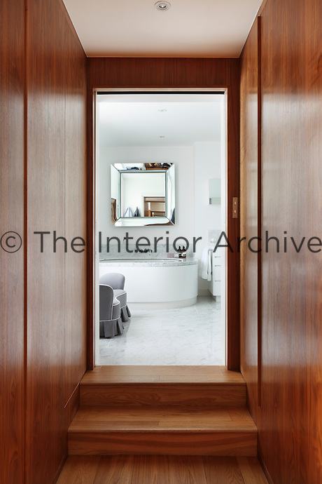A panelled corridor leads to a luxurious marble bathroom