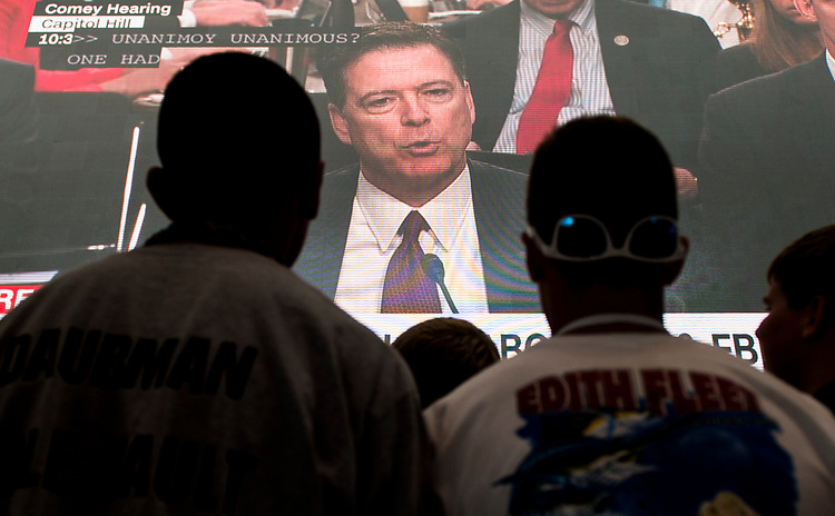 UNITED STATES - JUNE 8: A school group from Illinois touring the Newseum in Washington pauses to watch former FBI Director James Comey testify on the museum's large video screen during the Senate Select Intelligence Committee hearing on Thursday, June 8, 2017. (Photo By Bill Clark/CQ Roll Call)