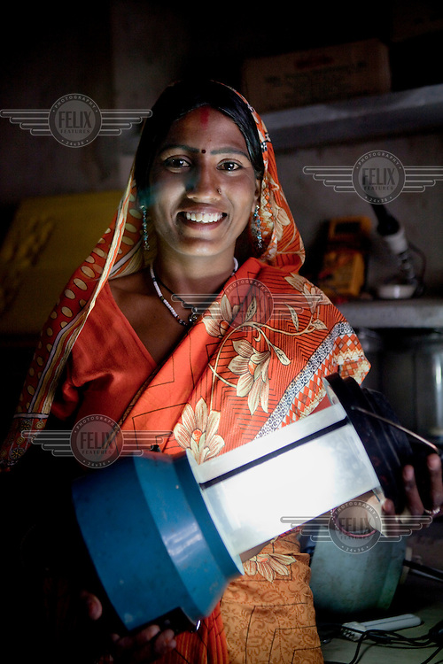 Santosh Devi, 19, repairing solar lanterns in her home workshop. She graduated from the Tilonia village Barefoot College (run by an NGO that provides education in rural communities), as a solar engineer in 2009. Since then she has supplied solar power to 20 homes in her village, making it the first village in India to be 100% solar powered. She also maintains the neighbouring village's solar power systems.