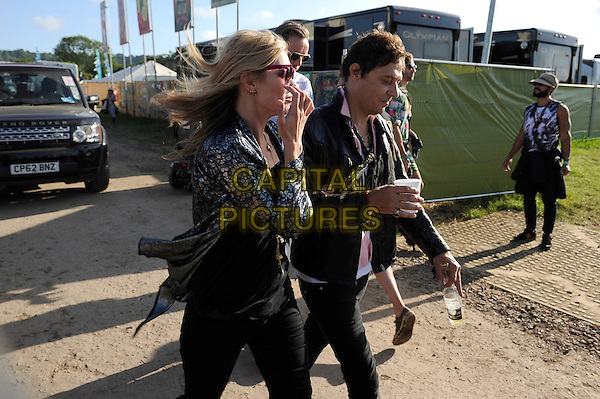 Kate Moss and Jamie Hince backstage at Glastonbury Festival, Worthy Farm, Pilton, Somerset, England. <br /> 29th June 2013<br /> half length sunglasses shades black side profile leather jacket print shirt jeans denim married husband wife cup drink beverage <br /> CAP/MAR<br /> &copy; Martin Harris/Capital Pictures