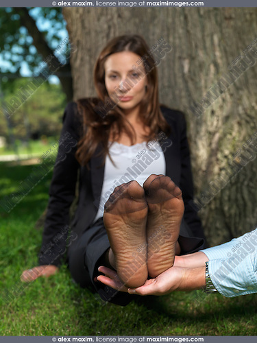 Young businesswoman feet resting on male hands. Footwear concept. Focus on the feet.