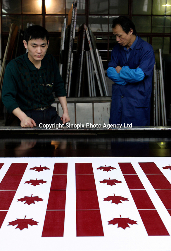 Workers man the a screen printing machine making Canadian national flags at the Shanghai Flag Factory in Shanghai, China. A majority of flags used around the world are produced in China due to its low costs, however state-owned factory like this one are out competed by smaller private firms who are more flexible and cheaper..26-APR-04