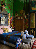 The headboard in the master bedroom is made of faux-marble pilasters and a pair of Indian pierced-wood doors and the mural of a Persian landscape is by Gwynn Griffith's son Greg Mannino