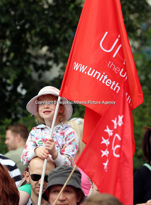 Swansea, UK. Thursday 10 July 2014<br /> Pictured: A young girl holding a Unite Union flag at Castle Square Gardens, Swansea, south Wales.<br /> Re: Strikes are taking place across the UK in a series of disputes with the government over pay, pensions and cuts, with more than a million public sector workers expected to join the action.<br /> Firefighters, librarians and council staff are among those taking part from several trade unions, with rallies taking place across the UK.