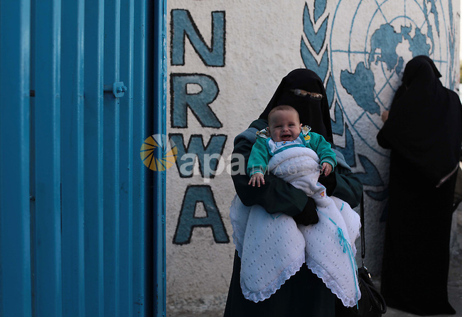 A Palestinian woman carries her son during a protest a the decision made by the United Nations Relief and Works Agency (UNRWA) to reduce food aid delivered to the Gaza Strip in front of the UNRWA headquarters in Gaza City on April 9, 2014. Photo by Ashraf Amra