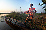 See Kim Lang, 15, poses after going fishing at dawn in the village of Phar Thruey in northern Cambodia.