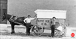 Two employees of the City Ice Co. pose with their horse-drawn delivery wagon. Notice the blocks of ice; one being held by the employee and the other handing from the back of the wagon.