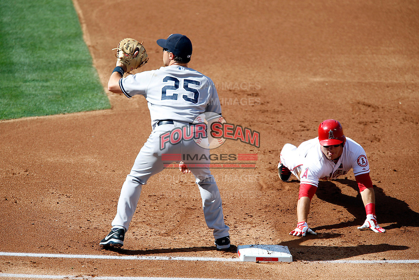 Mike Trout #27 of the Los Angeles Angels dives back to first base ahead of the throw to Mark Teixeira #25 of the New York Yankees during a game at Angel Stadium on June 15, 2013 in Anaheim, California. (Larry Goren/Four Seam Images)