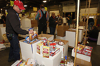 "Friday, February 15, 2013.   Volunteer Jerry Trodden puts one of the 144 bags of hot dog buns into a box of other food to be sent to Nome during the ""people food"" drop at Airland Transport in Anchorage."