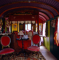 The bohemian interior of this period showman's wagon has been painted in rainbow colours