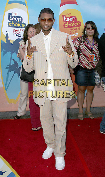 USHER.The 2004 Teen Choice Awards held at The Universal Ampitheatre in Universal City, California .August 8, 2004.full length, beige, cream suit, stripes, pointing, peace sign, gesture, white trainers.www.capitalpictures.com.sales@capitalpictures.com.Supplied By Capital Pictures