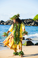 Kahiko hula dancer in yellow costumr with maile lei.