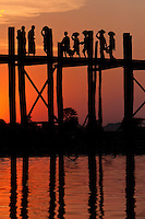Myanmar, Burma, Mandalay, Amarapura.  Burmese Walking Home over the U Bein Bridge at the end of the day.  The teak footbridge is 200 years old, and 1300 yards long.