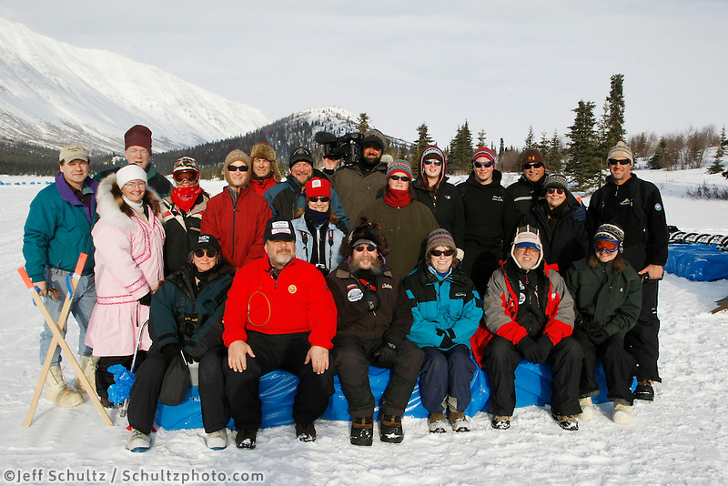 Race Volunteers , tourists and the Rainy Pass lodge owner pose for a group photo at the Rainy Pass checkpoint in the Alaska Range