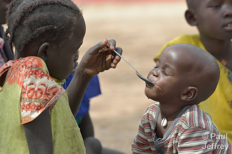 A girl feeds her sibling as part of a supplemental feeding program for malnourished children and mothers run by the clinic of the Loreto School in Rumbek, South Sudan. The school is run by the Institute for the Blessed Virgin Mary--the Loreto Sisters--of Ireland.