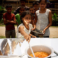 A young girl cooks for the first time with a solar cooker during a cooking competition at a Bhutanese refugee settlement. All the entrants were given a solar cooker to take home with them after the event and the winner received a pressure cooker. With the financial help of the Dutch Council for Refugees, a total of 6,300 solar cookers will be distributed amongst the Bhutanese refugees living in the region. The solar cookers consist of a reflective, aluminium, parabolic-shaped device that concentrates the sun's rays onto cooking pots placed on a frame in the centre of the dish. The dish has to be adjusted to the new position of the sun around every 10 minutes. It takes about 55 minutes to prepare a cooked meal on a sunny day and it is hoped that using the solar cookers will alleviate pressure on resources and reduce kerosene consumption by 75%...