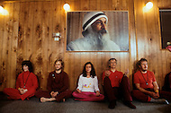 Wasco, Oregon, January 1984: Disciples meditate under the portrait of Bhagwan Rajneesh hanging on the wall. Rajneeshpuram, was an intentional community in Wasco County, Oregon, briefly incorporated as a city in the 1980s, which was populated with followers of the spiritual teacher Osho, then known as Bhagwan Shree Rajneesh. The community was developed by turning a ranch from an empty rural property into a city complete with typical urban infrastructure, with population of about 7000 followers.