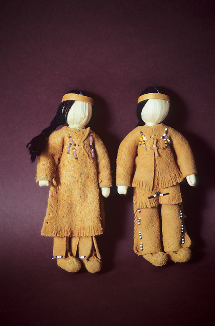 Pair of Ute children's toy dolls of a man and woman dressed in traditional clothing made from buckskin