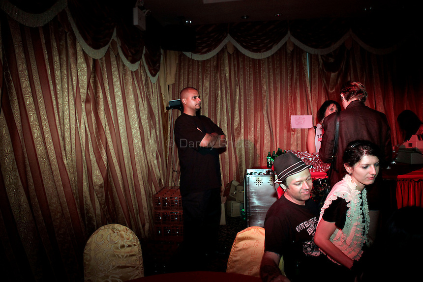 A Madam Wong security staff member watches over the party at Madam Wong night club. By day Golden Unicorn is a traditional Chinese restaurant, but it is transformed into Madam Wong, a trendy Manhattan club at night. ..Danny Ghitis for The New York Times