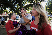 NWA Democrat-Gazette/CHARLIE KAIJO Rev. Sara Milford talks to Mike Graham (from left) while passing out flowers during a rally, Friday, October 5, 2018 at the town square in Bentonville. Volunteers distributed 51 flowers to honor the 51 women, men and children who lost their lives due to domestic violence last year.<br /><br />A rally was held concerning domestic violence to recognize October as Domestic Violence Awareness Month<br /><br />&quot;Of the 51 people who were killed last year, they came across from all demographics. The youngest was an infant, an unborn child. The eldest was a 74 year old woman. One victim was a nurse. Another was a day care worker, and another was a police officer responding to the domestic violence incident,&quot; said Antonella Kinder, development coordinator for the NWA Women's Shelter. &quot;All of that to say that domestic violence doesn&Otilde;t discriminate.&Oacute;