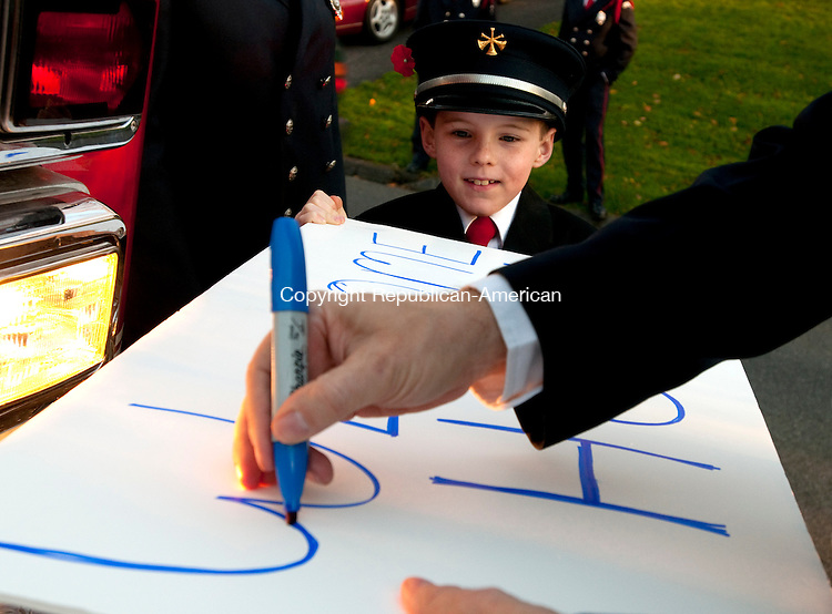 SOUTHBURY, CT, 05 NOVEMBER 2010-111010JS02--Jon Bicking, son of Southbury Volunteer firefighter Teresa Bicking, looks on as firefighter Brian Jones writes out a welcome home sign prior to the arrival home of United State Air Force soldier Michael Thompson of Southbury on Wednesday from his service in Afghanistan.<br />  Jim Shannon Republican-American