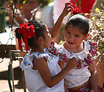 Girl adjusts the ribbon in her friend's hair prior to festival
