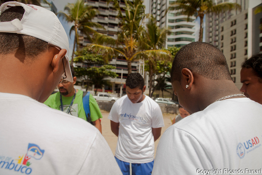 Young men under supervised probation praying before soccer game at Boa Viagem beach in Recife, Pernambuco state, Northeast Brazil. Instituto Empreender, partner of USAID/Brasil, uses sport as a means for strengthen basic principles like rules, authority, leadership, anxious control.