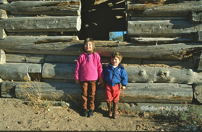 Boy and girl in front of old log cabin