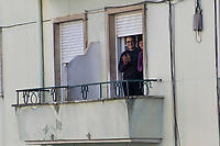 LISBON, PORTUGAL - April 12: Neighbors on their windows looking down to a violinist who plays to cheer up the quarantine on April 12, 2020 in Lisbon, Portugal. <br /> The covid-19 pandemic has spread at breakneck speed, and quarantining more than 3.9 billion people, closed in their homes - more than half of the planet's population.<br /> Photo by Luis Boza/VIEWpress vía Getty Images