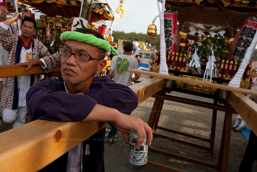 Portrait of a mikoshi supporter drinking a beer during the Hamaorisai Matsuri that takes place on Southern Beach in Chigasaki, near Tokyo, Kanagawa, Japan Monday July 18th 2011. The festivals marks the celebration of Marine Day and the rescuing of a divine image that was washed ashore in the area. Over thirty Mikoshi or portable shrines are carried through the night from surrounding shrines to arrive on the beach for sunrise. There they are blessed and then carried into the surf to purify them.