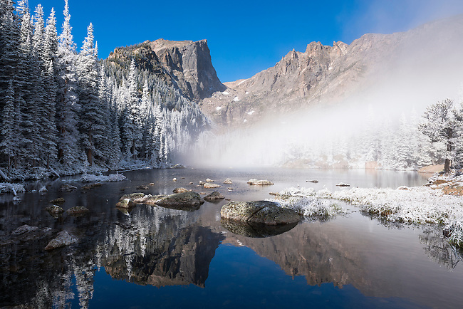 Hallett Peak and Flattop Mtn through fog reflected in Dream Lake, frosty September morning in Rocky Mountain National Park, Colorado, USA