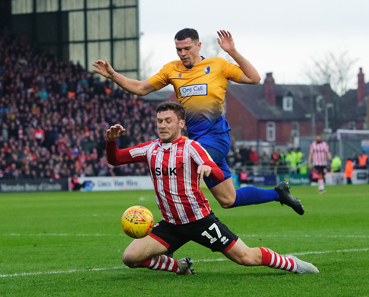 Lincoln City's Shay McCartan is fouled by Mansfield Town's Matt Preston<br /> <br /> Photographer Chris Vaughan/CameraSport<br /> <br /> The EFL Sky Bet League Two - Lincoln City v Mansfield Town - Saturday 24th November 2018 - Sincil Bank - Lincoln<br /> <br /> World Copyright © 2018 CameraSport. All rights reserved. 43 Linden Ave. Countesthorpe. Leicester. England. LE8 5PG - Tel: +44 (0) 116 277 4147 - admin@camerasport.com - www.camerasport.com