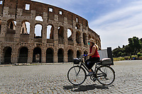 Rome 17/5/2020 <br /> A woman, wearing a mask, rides a bicycle in front of the coliseum during the second phase of lockdown measures decided by italian government due the coronavirus, covid-19, pandemic . <br /> Restaurants, bars and most of the commercial activities will be reopened on 18 May . <br /> Photo Andrea Staccioli / Insidefoto